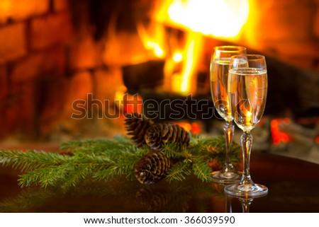 Two glasses of sparkling white wine and fir branches in front of warm fireplace. Romantic, cozy relaxed magical atmosphere near fire. New Year or Christmas concept - stock photo