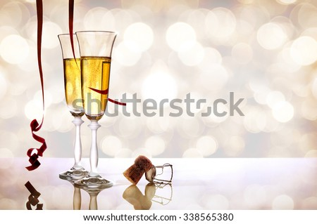Two glasses of sparkling white wine on white methacrylate table with bokeh background. With red ribbons hanging and cork. Party concept.Horizontal composition. Front view - stock photo