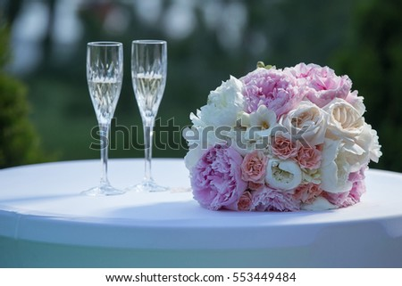 two glasses of sparkling wine and bouquet of the bride.