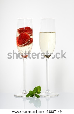 Two glasses of sparkling wine and strawberry on white - stock photo