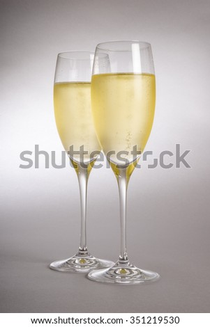 Two Glasses of Sparkling Wine Backlit and on Grey Background - stock photo