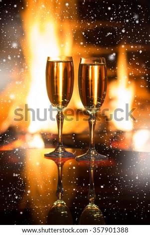 Two glasses of sparkling wine in front of warm fireplace. Cozy relaxed romantic atmosphere near fire of fireplace. Holiday, Christmas o Valentines day concept. Background with shimmering wine.