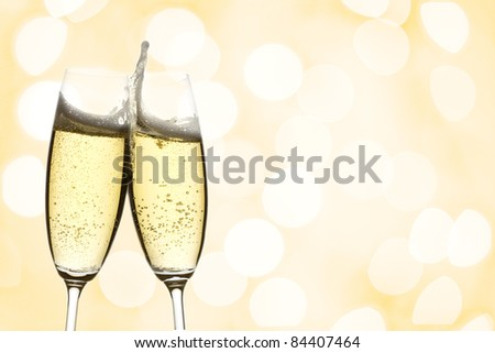 two glasses of sparkling wine with copyspace and abstract lights background - stock photo