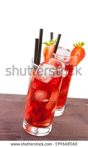 two glasses of strawberry cocktail with ice on old wood table and white background - stock photo