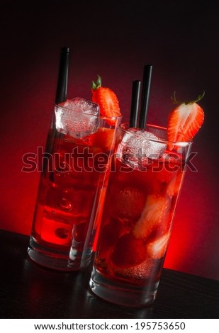 two glasses of strawberry cocktail with ice on wood table and a red gradient background - stock photo