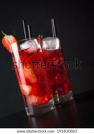 two glasses of strawberry cocktail with ice on wood table and black background