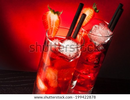 two glasses of  strawberry cocktail with ice on wood table and red gradient background - stock photo