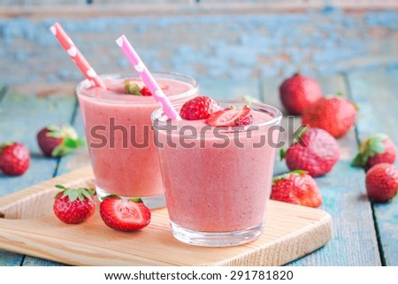 Two glasses of strawberry smoothie with straws on a wooden board - stock photo