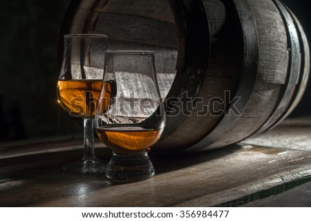 Two glasses of strong alcohol, near the oak barrel