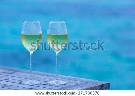 Two glasses of tasty white wine at sunset  - stock photo