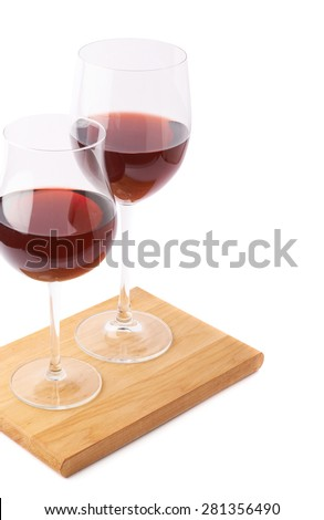 Two glasses of the red wine over the serving wooden boards, composition isolated over the white background, framed as a copyspace background composition - stock photo