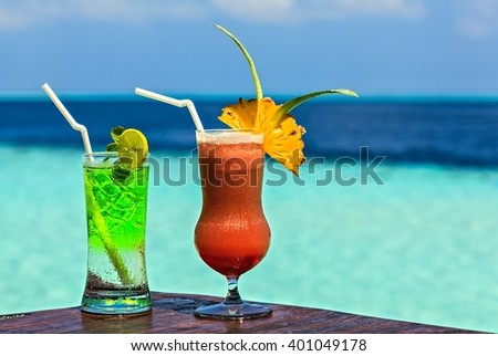 Two glasses of the soft drink are on a beach table (Maldives, The Indian Ocean) - stock photo