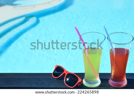 Two glasses of tropical fruit juice and sunglasses beside blue pool -- Summer vacations concept  - stock photo