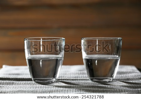 Two glasses of water on table on wooden background - stock photo