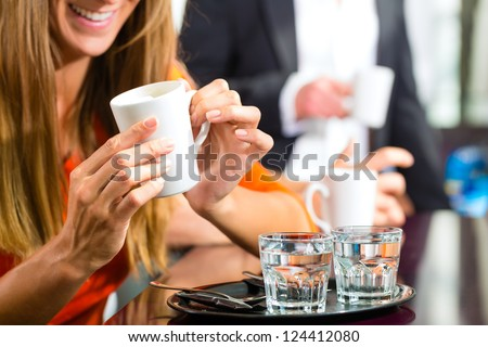 Two glasses of water standing on a tablet in the cafe a young woman drinking coffee - stock photo