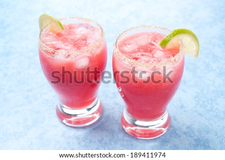 Two glasses of watermelon cocktail with brown sugar and lime, horizontal, close-up - stock photo