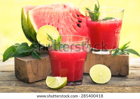 Two glasses of watermelon smoothies with lime and mint  - stock photo