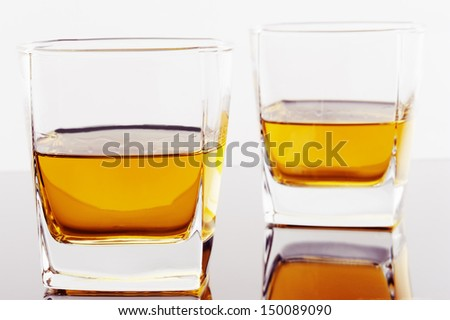 two glasses of whiskey against white background