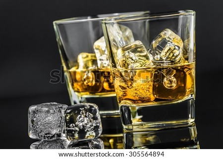 two glasses of whiskey near ice cubes on dark background, time of relax with whisky - stock photo