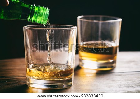 Two glasses of whiskey on a wooden table