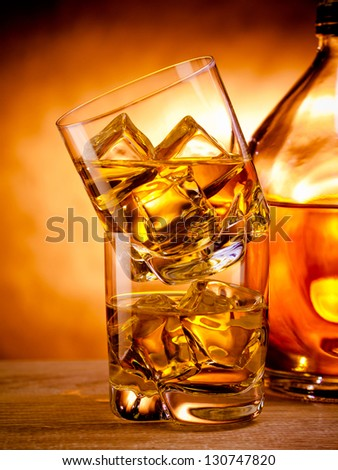 Two glasses of whiskey on the rocks and a bottle - stock photo