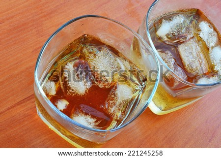Two glasses of whiskey over ice on the table. - stock photo