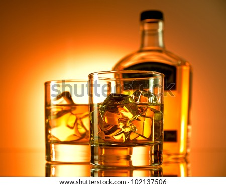 Two glasses of whiskey with a bottle in the background