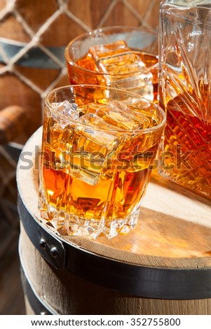Two glasses of whiskey with ice and decanter on a wooden barrel