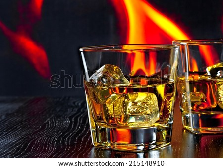 two glasses of whiskey with ice cubes in front of the flame on wood table with space for text - stock photo