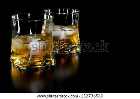 two glasses of whiskey with ice with space for text on black background - stock photo