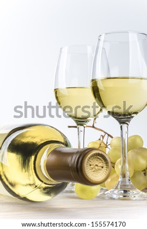 Two glasses of white wine and a bottle - stock photo