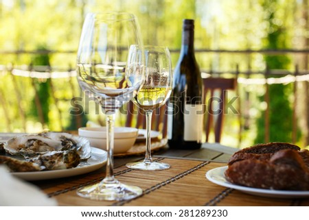 Two glasses of white wine and a bottle on the table.