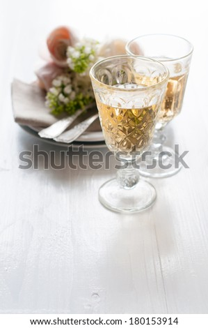 Two glasses of white wine and festive fine dining table setting with a bouquet of flowers on a white table - stock photo