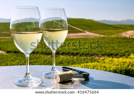 two glasses of white wine on table overlooking California wine country on sunny, cloudless day - stock photo