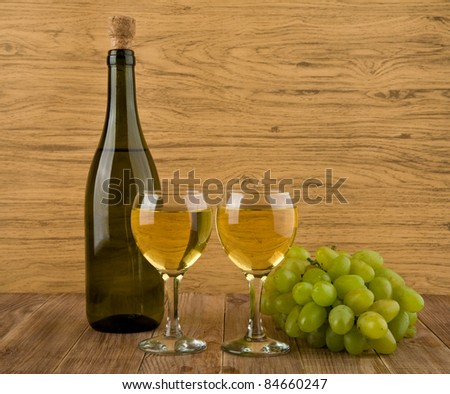 two glasses of wine and bottle on a wooden table