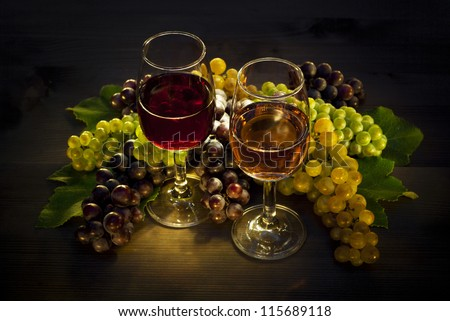 two glasses of wine and grapes on wooden - stock photo