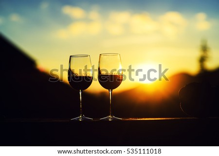 Two glasses of wine at sunset dramatic sky on mountain landscape background