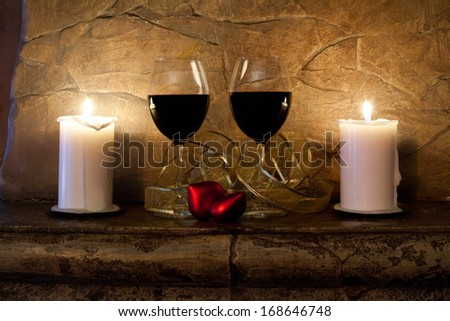 Two glasses of wine, candles and teddy red heart on stone wall background. Valentines day. Romantic still-life.  - stock photo
