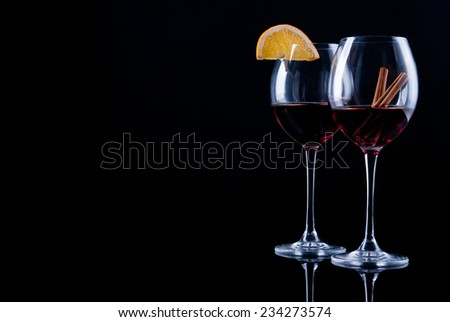 Two glasses of wine decorated with a slice of orange and cinnamon sticks black background - stock photo