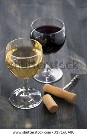 two glasses of wine on a wooden table, vertical