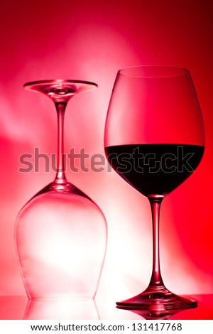 two glasses of wine on red background