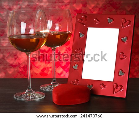 Two glasses of wine, red heart and photo frame. Valentines day. Romantic still-life. - stock photo