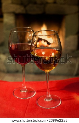 Two glasses of wine. Red tablecloth. Fireplace. Chimney. (vintage paper background, retro style). - stock photo