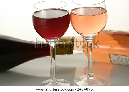 Two glasses of wine with bottles