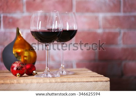Two glasses of wine with christmas toys on wall background