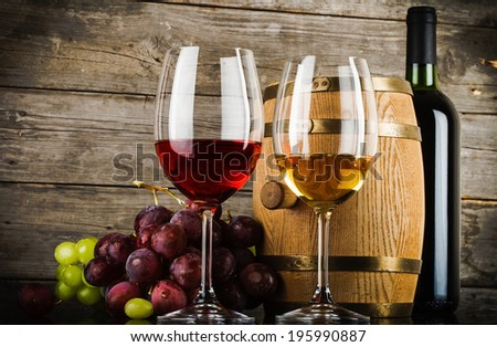 two glasses of wine with fresh fresh grapes, bottle and barrel in front of old grunge wooden planks
