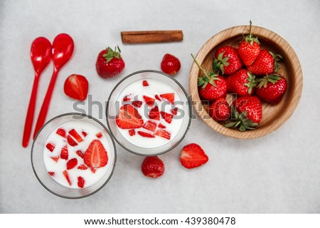 Two Glasses of Yogurt,Fresh Strawberries in the Wooden Plate with Plastic Spoons,Cinnamon on the White Paper.Breakfast Organic Healthy Tasty Food.Cooking Vitamins Ingredients.Summer Fruits.Top View - stock photo