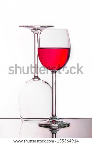 two glasses paired one with rose wine on glass surface