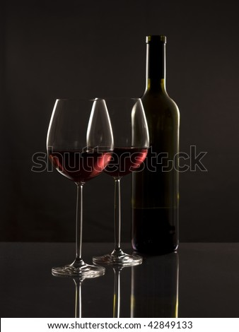 Two glasses red wine and one bottle with reflection on a darck background