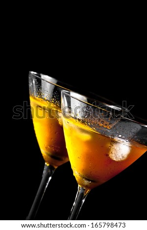 two glasses tilted of fresh cocktail with ice on black background with space for text